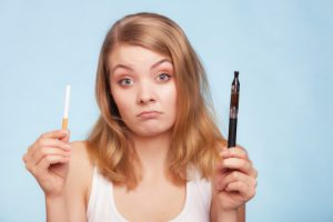 Girl holding traditional and electronic cigarette