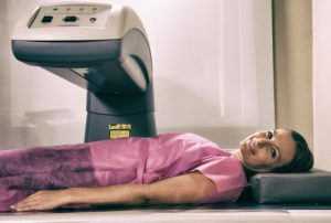 Woman in her 40s undergoing scan at bone densitometer machine