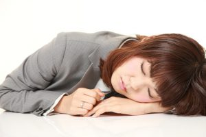 young Japanese businesswoman sleeping on the desk