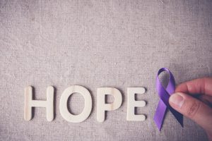 fingers holding Purple ribbon with HOPE wooden letter, toning, A