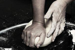 Hands kneading a dough.