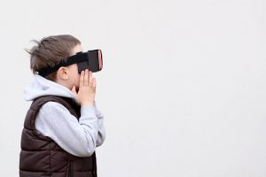 Fascinated little boy using VR virtual reality goggles