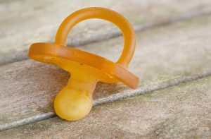 Dirty rubber pacifier on a wooden surface. Closeup