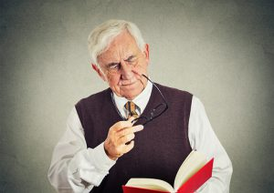 senior elderly man holding book, glasses having eyesight problems unable to read